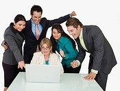 Four business executives surrounding a businesswoman working on a laptop (thumbnail)