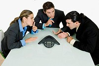 Two businessmen and a businesswoman having a telephone conference in a boardroom
