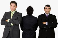 Rear view of a businessman standing with two businessmen with their arms crossed
