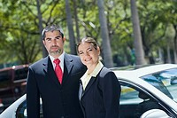Portrait of a businesswoman standing with a businessman in front of a car