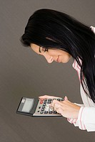 Side profile of a businesswoman holding a calculator