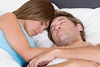Close-up of a mid adult man sleeping on the bed with a young woman