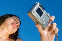Low angle view of a girl taking a photograph of herself
