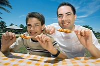 Portrait of a mid adult man with his son eating sausages in a picnic
