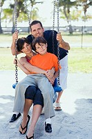 Mid adult woman sitting on a swing with her son and a mid adult man pushing them