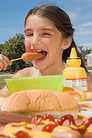 Girl eating a sausage in a picnic
