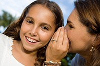 Close-up of a mid adult woman whispering into her daughter´s ear