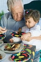 Senior man feeding his granddaughter with a fork
