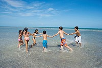 Children playing with holding each other hands on the beach