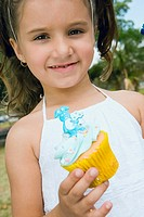 Portrait of a girl holding a cupcake and smiling