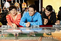 Mature woman with a mid adult man and a teenage girl leaning on a casino