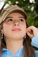 Close-up of a young woman wearing headphones and looking up