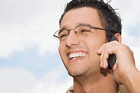 Close-up of a young man talking on a mobile phone and smiling