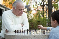 Grandfather Playing Chess with Grandson on Street Corner