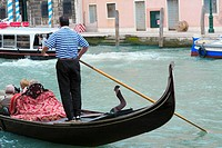 Man standing on a gondola in a canal, Grand Canal, Venice, Italy