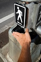 Close-up of a man's hand adjusting a pedestrian crossing signboard, Honolulu, Oahu, Hawaii Islands, USA