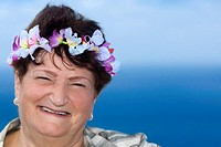 Portrait of a mature woman wearing a wreath and smiling, Diamond Head, Waikiki Beach, Honolulu, Oahu, Hawaii Islands, USA