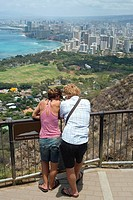 Rear view of a man and a woman standing at an observation point, Diamond Head, Waikiki Beach, Honolulu, Oahu, Hawaii Islands, USA