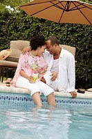 Playful couple laughing poolside
