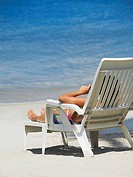 Rear view of a woman lying on a lounge chair on the beach, South West Bay, Providencia, Providencia y Santa Catalina, San Andres y Providencia Departm...