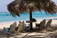Beach chairs under palapa on the beach, Coral Cay, Dixon Cove, Roatan, Bay Islands, Honduras