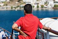 Rear view of a mid adult man standing on a yacht and looking at a view, Patmos, Dodecanese Islands, Greece