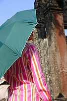 Rear view of a woman under an umbrella in a temple, Ta Prohm Temple, Angkor Wat, Siem Reap, Cambodia