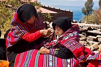 Mid adult woman grooming a bride for wedding, Taquile Island, Lake Titicaca, Puno, Peru