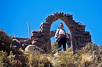 Portrait of a young woman standing under a stone arch, Taquile Island, Lake Titicaca, Puno, Peru