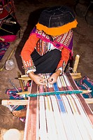 Woman weaving in a loom, Aguanacancha, Peru