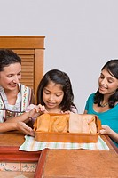 Mid adult woman with her two daughters smiling with a tray of breads in the kitchen