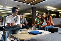 Students in library sitting on sofas studying