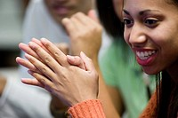 Close_up of a smiling young woman with hands clasped