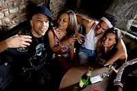 Young men and women in hip_hop fashion partying at a bar