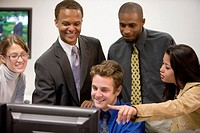 Close_up of office workers gathered around computer