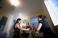 Three women having drinks in kitchen