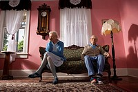 Senior couple sitting on opposite ends of couch