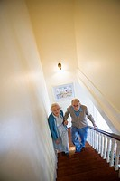 Senior couple helping one another carefully climb up stairs