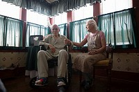 Senior woman sitting next to feeble senior man in wheelchair in bedroom