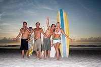 Surfer dudes and girl posing on beach at sunrise with surfboards