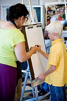 An art teacher showing young boy how to draw on an easel in art class