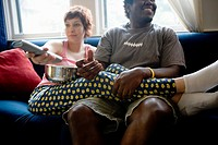 Young inter_racial couple sitting on a sofa watching television