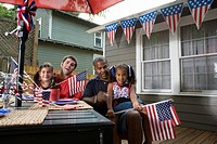Two young girls with dads at 4th of July cookout waving American flags