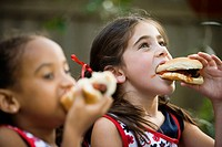Close_up of girls eating hotdogs