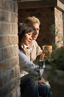 Mature inter_racial couple holding coffee mugs sitting on front steps of their house