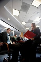 Low angle view of business men and women at a presentation in a formal conference room