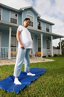 Portrait of pregnant woman standing on yoga mat in front of house