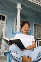 Young Asian woman sitting on a rocking chair reading a book in front of house