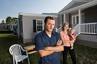 Portrait of a blue_collar man standing in front of a trailer home with wife and baby
