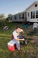 Man sitting on an ice chest holding a drink bottle in front of trailer home